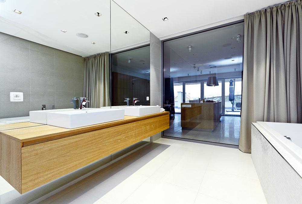 Rodičovskej kúpeľni dominuje sklenená stena, ktorá vizuálne spája dennú anočnú zónu bytu.