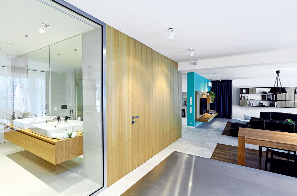 Sklenenú stenu na celú výšku miestnosti navrhli architekti na presvetlenie kúpeľne vstrede dispozície.