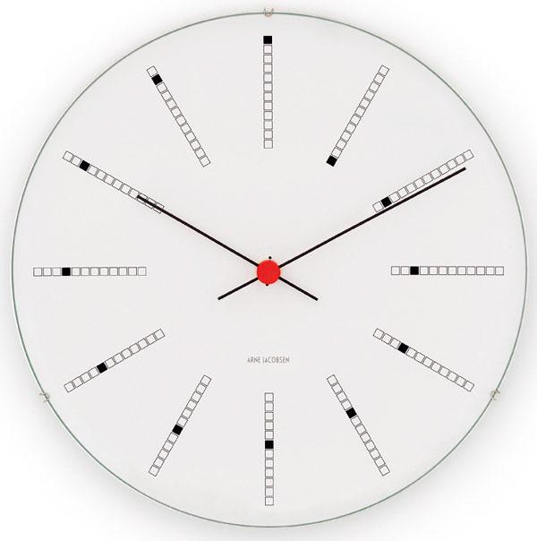 """Hodiny Bankers navrhol architekt Arne Jacobsen na sklonku života v roku 1971, keď pracoval na návrhu budovy Národnej banky v Kodani. V súlade s jeho filozofiou """"totálneho dizajnu"""" vytvoril pre bankárov všetko – od architektonickej tváre budovy až po kľučky na dverách, nástenné hodiny nevynímajúc. Bankers vynikajú nadčasovým pôvabom aj modernistickou efektivitou s letmým nádychom rafinovanej rozmarnosti. Tú predstavuje hravý ciferník so špirálovitým usporiadaním. Od 195 €, ROSENDAHL"""