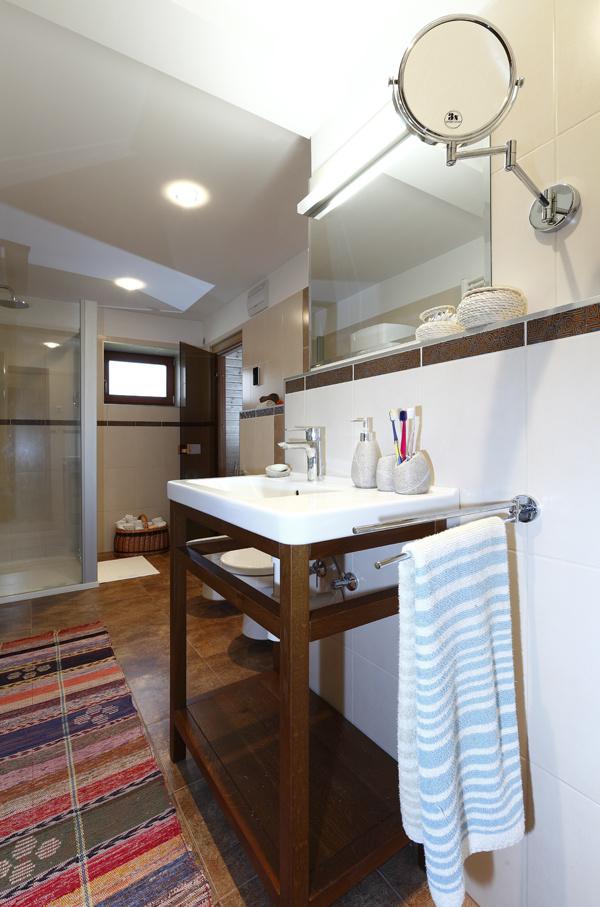 Vo veľkej modernej kúpeľni na prízemí sa snúbi súčasnosť s jemnými detailmi v tradičnom duchu. Za kúpeľňou je ukrytá fínska sauna.