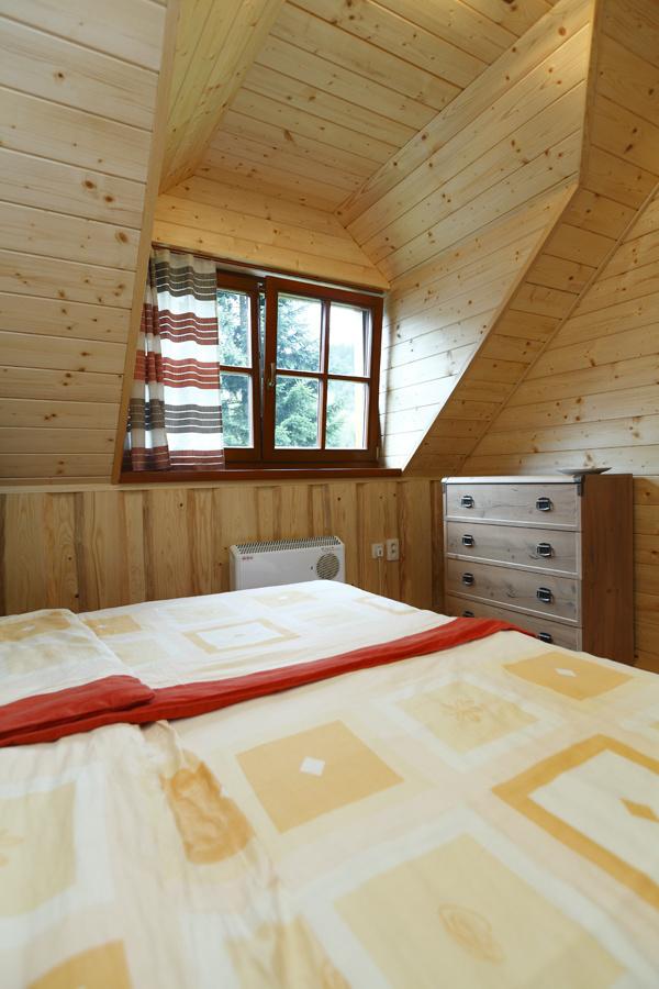 Jedna zo spální na poschodí s romantickou atmosférou pod šikmou strechou a vôňou dreva.
