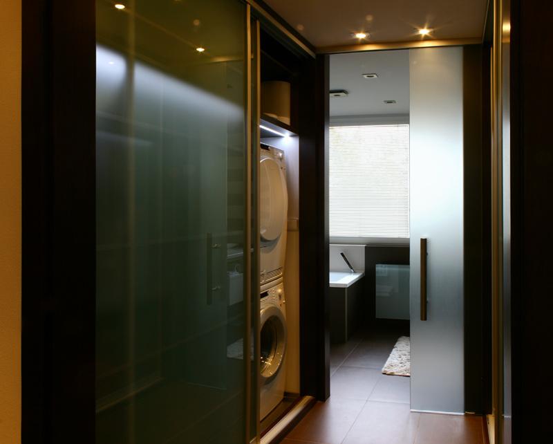 Práčka a sušička nezaberajú miesto v kúpeľni, ale sú skryté za posuvnými dvermi vstavanej skrine.
