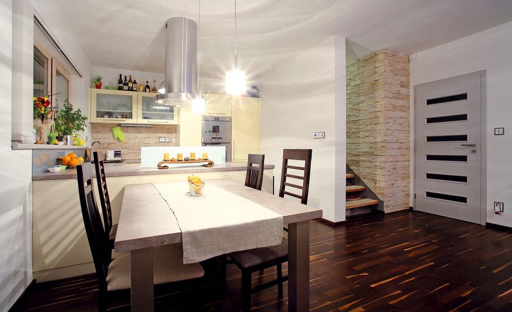 Kuchyňa vanilkovej farby je rovnako ako všetok nábytok vdome vyrobená na mieru. Nadväzuje na ňu jedálenské sedenie spriestranným stolom advoma druhmi stoličiek.