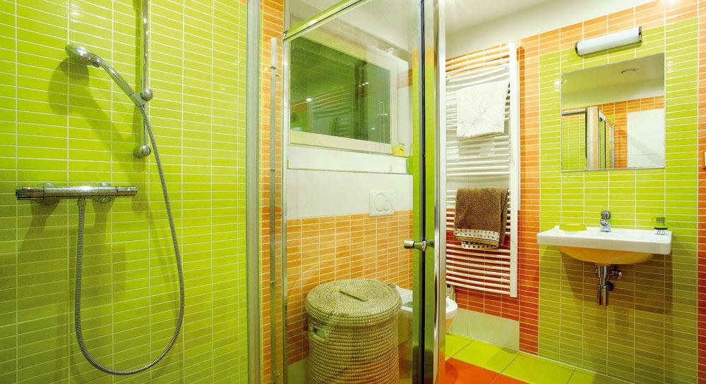 Vkúpeľni na prízemí sa majitelia rozhodli pre zasklený sprchovací kút. Zelenú farbu, ktorá je farbou podlažia, doplnili oranžovou.