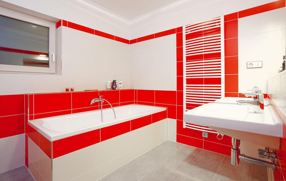 Druhá kúpeľňa na poschodí je ladená do výraznej oranžovočervenej abielej farby. Nechýba vnej vaňa ani dve umývadlá pre väčší komfort.