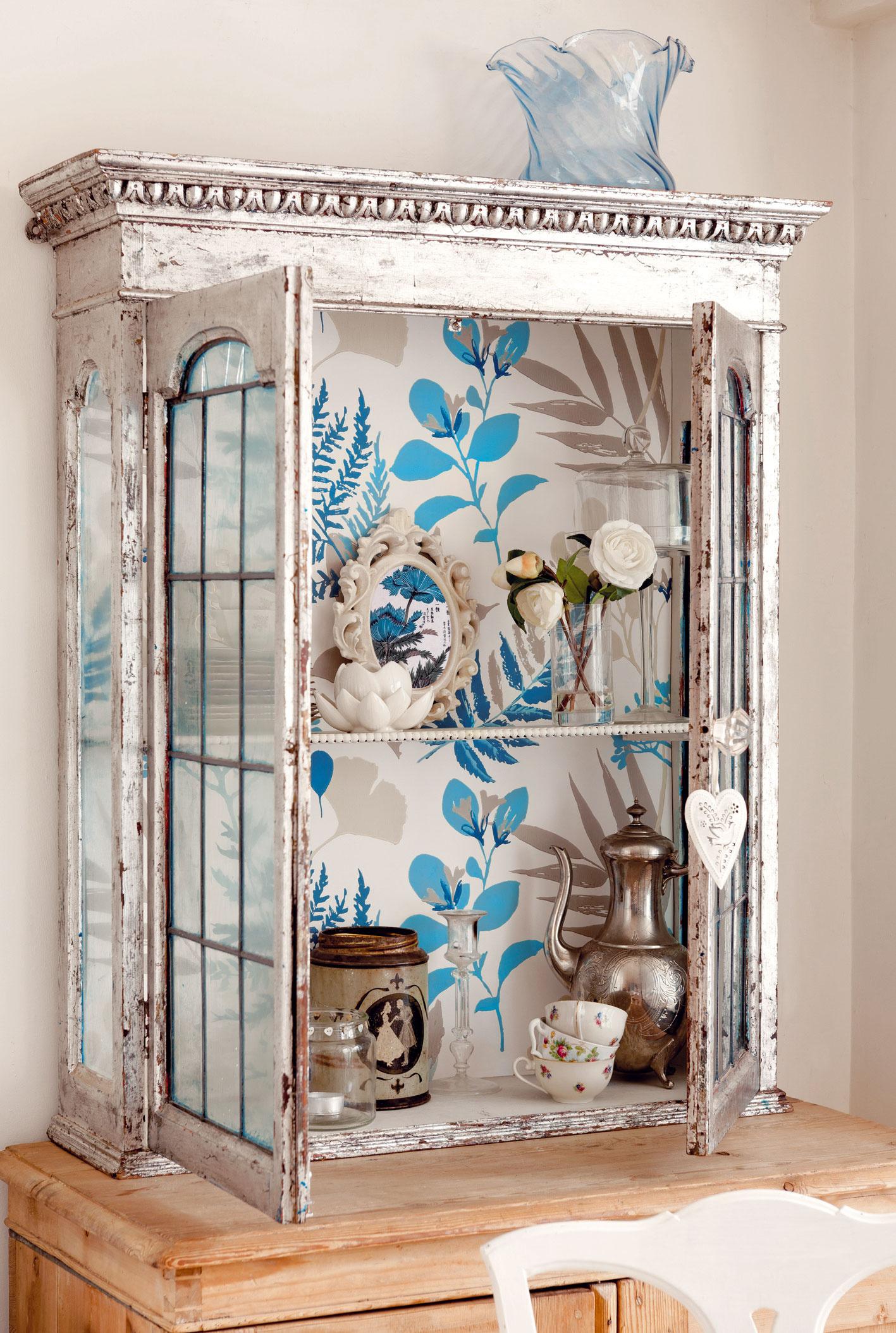 2 ROZKVITNUTÁ VITRÍNA  Otapetujte zadnú stenu starej vitríny. Samozrejme, musí mať sklené dvierka. Vtomto prípade jemné modré vzorynevtieravo kontrastujú svystaveným riadom. Tapetu alebo pevnejší baliaci papier so vzorom vyberajte tak, aby neprebíjali farby nádob, ale slúžili im len ako pozadie.