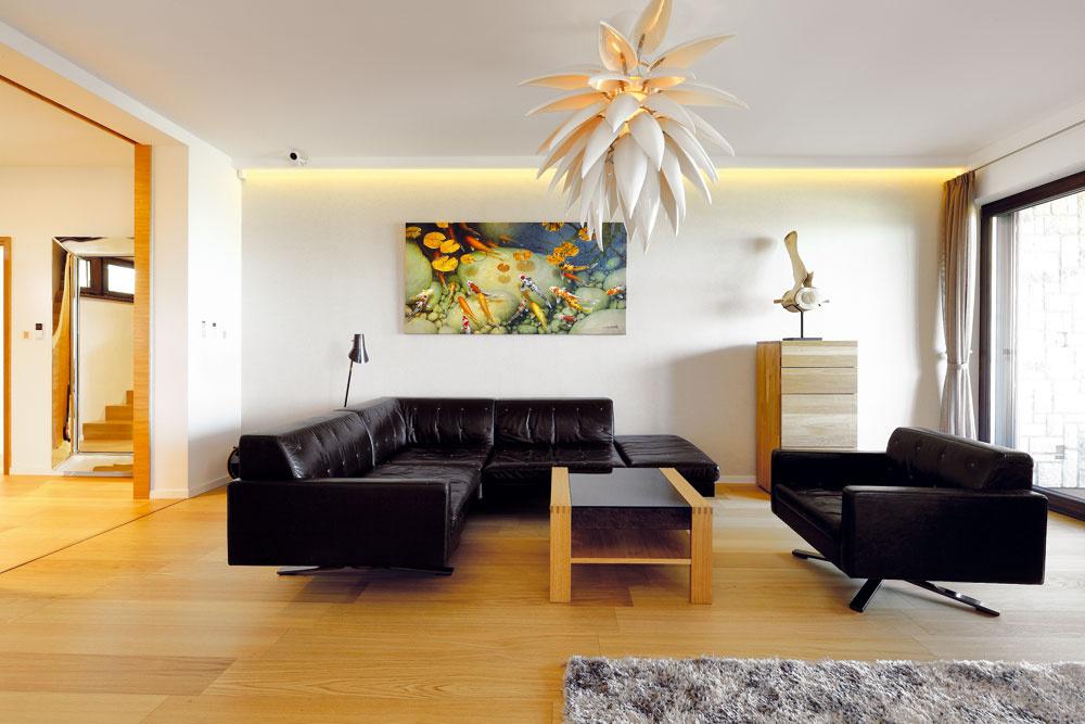 Vďaka drevu, prírodnej farebnosti astarostlivo vybraným doplnkom pôsobí interiér príjemným útulným dojmom, hoci sú rozmery obývačky naozaj úctyhodné.