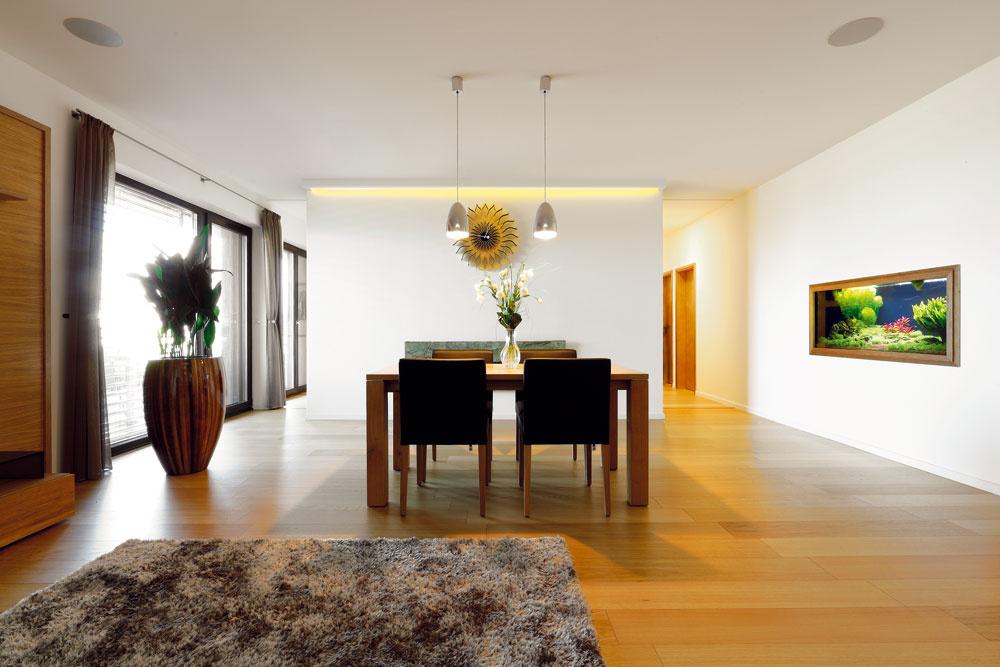 Sotvoreným denným priestorom obývačky ajedálne susedí kuchyňa oddelená polpriečkou – vľavo sa popri zasklenej stene vchádza do kuchyne, vpravo vedie chodba kďalším izbám.