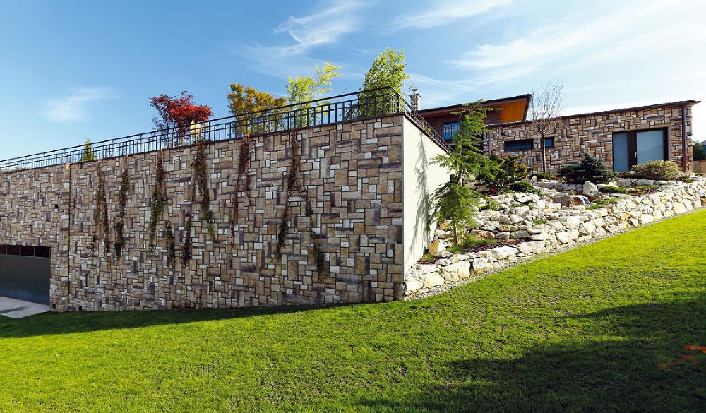Vysoký oporný múr, ktorý bol potrebný na vytvorenie rovinatej časti záhrady vstrmom kopci, časom obrastú popínavé rastliny.