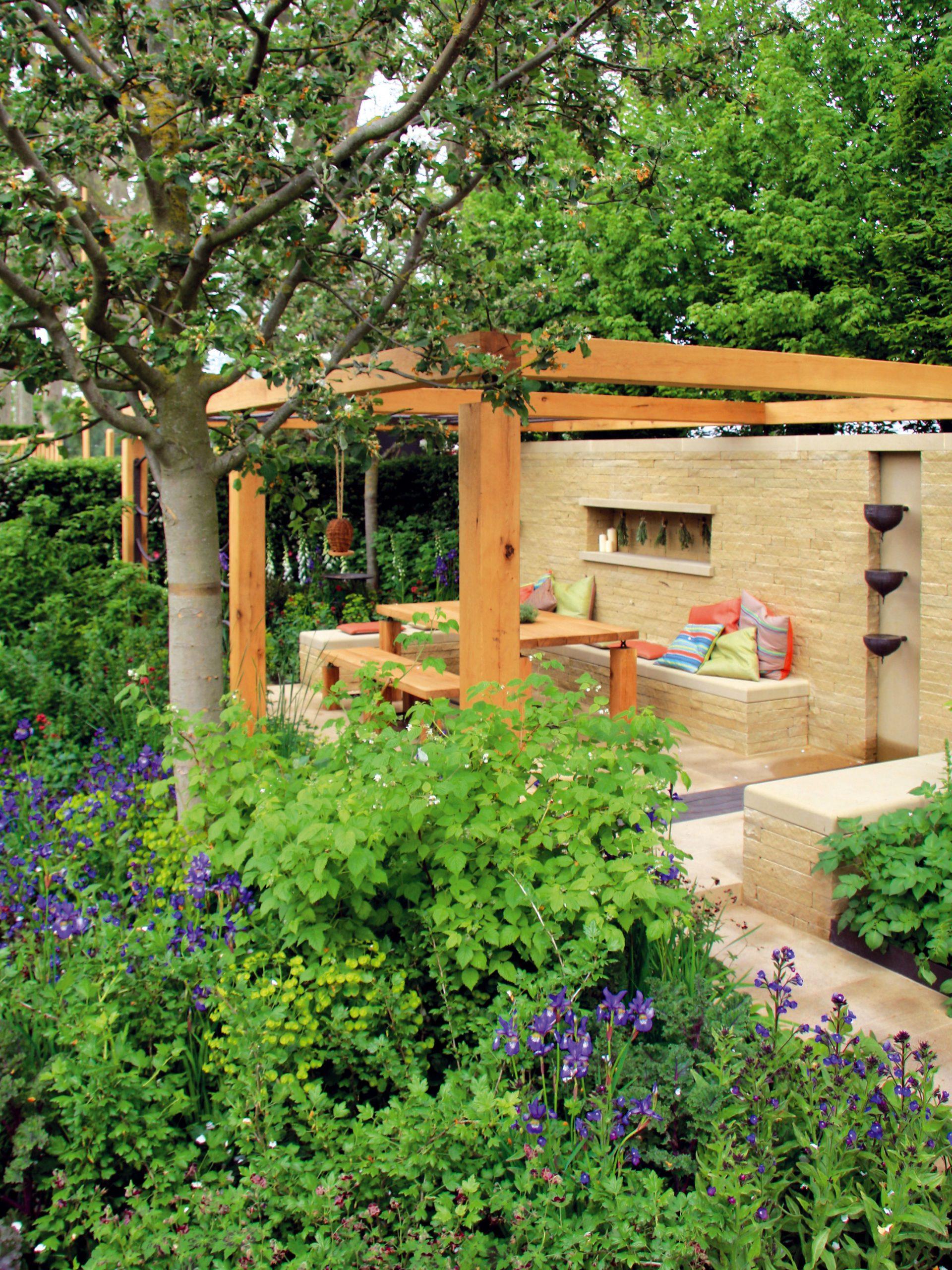 Na pergole so záhradným sedením sú šikovne skombinované drevo akameň. Príjemným akcentom sú farebné vankúše.