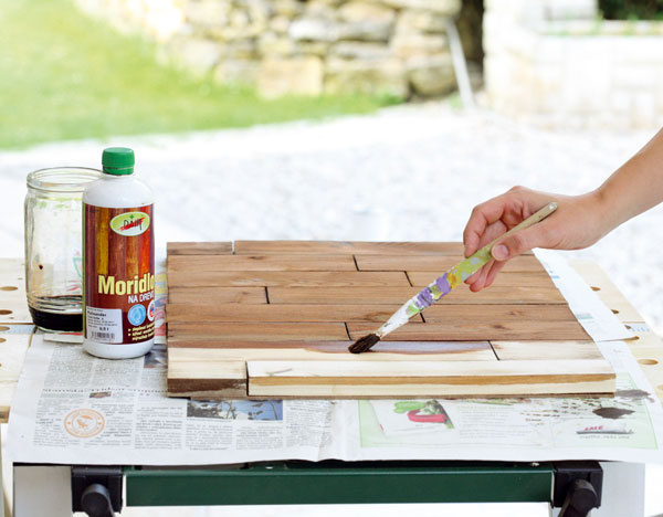 Latky uložte nasucho na sololit, ktorý bude tvoriť zadnú stenu na dvierkach skrinky, anamorte ich moridlom zriedeným svodou. Odtieň moridla najskôr odskúšajte na prebytočnej latke.