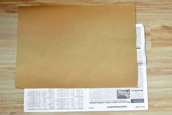 Podľa novinovej dvojstrany vystrihnite rovnako veľký hárok baliaceho papiera. Vrecko bude pevnejšie aaj tvar bude držať lepšie.