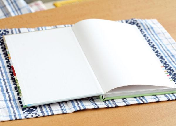 Odstrihnite približne polovicu zutierky tak, aby jej okraje presahovali knihu asi o1,5 cm na výšku aasi o6 cm po bokoch. Odstrihnuté kraje endlujte. (Veľkosť odstrihnutej utierky, samozrejme, závisí od rozmerov knihy.)