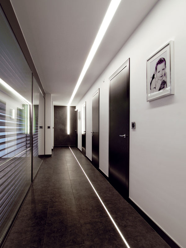 Chodba je osvetlená zaujímavým LED pásom vstrope, ktorý ako odraz pokračuje aj vpodlahe. Vnoci ostáva svietiť jemný pásik vpodlahe, atak na chodbe vytvára príjemné nočné orientačné tlmené svetlo.