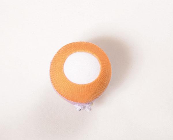 Na polystyrénovú guľu navlečte časť bielej ponožky a na ňu čiapočku z farebnej ponožky. Vo farebnej ponožke vystrihnite otvor v časti krku a prevlečte cezeň koniec bielej ponožky. Druhý koniec farebnej ponožky zošite v zadnej časti hlavy.