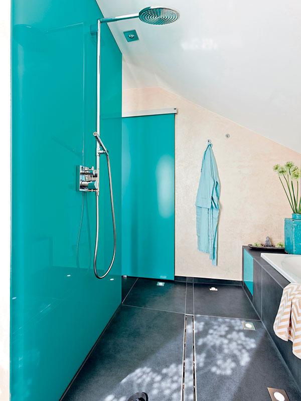 Inštalačná zástena obložená panelom ztyrkysového skla vytvára priestor na sprchovanie bez klasického sprchovacieho kúta. Voda odteká žľabom šikovne zabudovaným vpodlahe zveľkoplošných antracitovosivých dlaždíc.