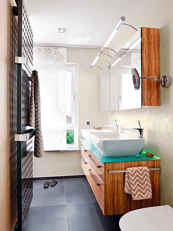Priestranné zásuvky vskrinkách pod umývadlami apoličky za zrkadlami nad nimi poskytujú dostatok odkladacieho priestoru – výslovne si ho želala domáca pani. Kombinácia tyrkysovej sbielou asivou je očakávane efektná aspojenie so svetlým drevom prekvapivo príjemné.