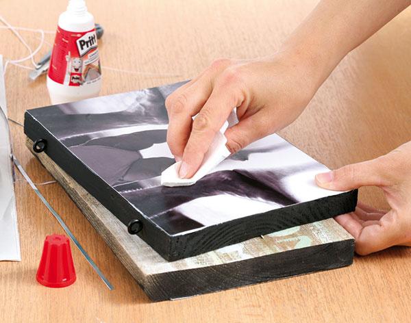 Na lepidlo priložte fotografiu a servítkou roztlačte lepidlo pod ňou, až kým povrch fotky nie je hladký. Ak použijete fotku s tenším papierom, môže sa zvlniť. Po vyschnutí sa však opäť vyrovná.