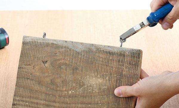 Z laty odpíľte požadovaný rozmer, v našom prípade to bolo 17 × 23 cm. Dosku vybrúste brúsnym papierom dohladka. Na vrchnej strane dosky v rovnakej vzdialenosti od krajov naznačte dva body, do ktorých vyvŕtate diery a do nich zaskrutkujte skrutky s háčikmi.