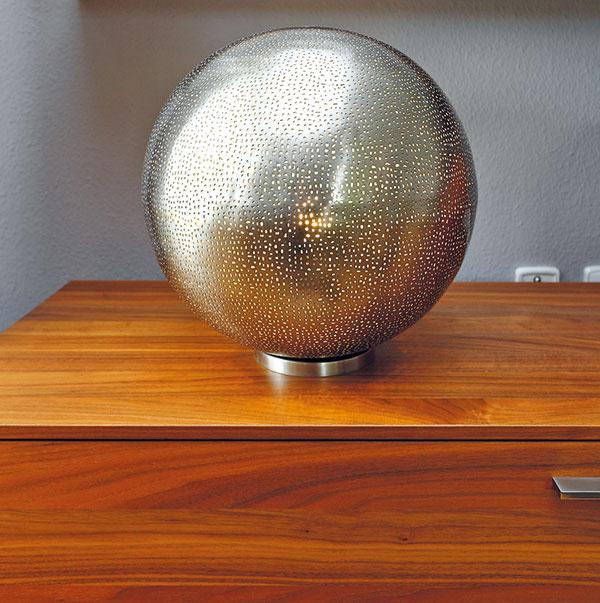 Doplnky príjemne osviežili jednoduchú obývačkovú zostavu zaujímavými tvarmi, materiálmi aj farbami. (Arabská stolová lampa Round, cena od 99 € podľa rozmerov, www.teakshop.sk)