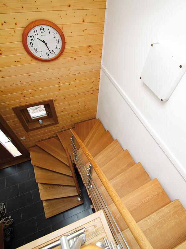 Dubové schodisko je dominantou vstupného priestoru – vďaka jeho vzdušnosti aveľkému strešnému oknu pôsobí priestor voľne aje zaliaty prirodzeným svetlom.