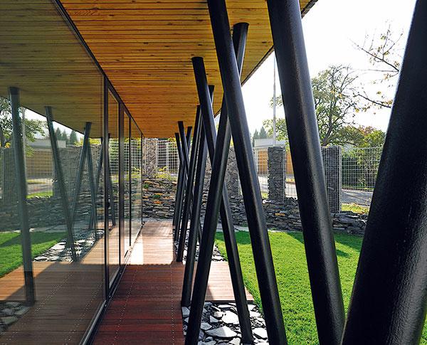 Suterén domu, obrátený veľkou zasklenou stenou do záhrady, lemujú oceľové stĺpy santikoróznym náterom – nosný systém je tu zároveň originálnou dominantou vzhľadu.