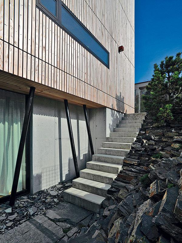 """Prudko sa zvažujúci terén využili na vytvorenie prirodzene pôsobiacej skalky, ktorá postupne zarastá vegetáciou. (Betónové schody spájajú """"vonkajškom"""" prízemie domu so záhradou na úrovni suterénu.)"""