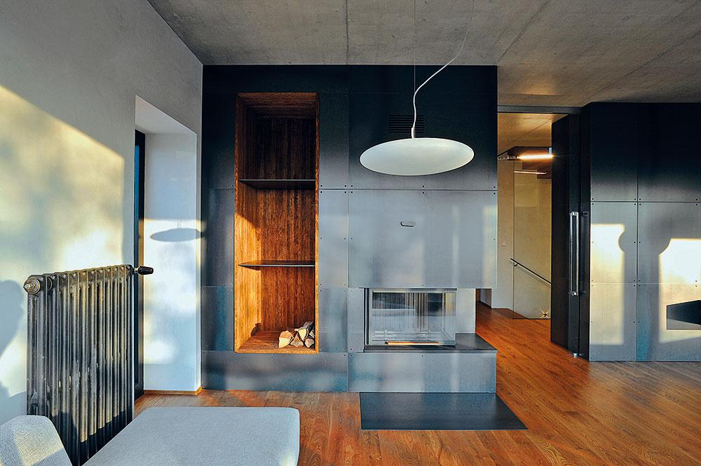 Kozub, vktorom sa kúri klasicky, drevom, je na opačnom konci obytného priestoru, naproti kuchyni. Bol želaním domáceho pána, je však len doplnkovým zdrojom tepla. Ako primárny zdroj vykurovania domu slúži tepelné čerpadlo. Teplo sa do interiéru odovzdáva kombináciou podlahových konvektorov, podlahového vykurovania aradiátorov.