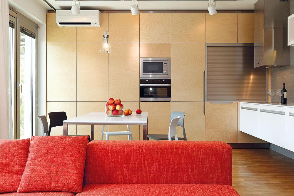 Minimalistická kuchyňa K zaujímavým prvkom zariadenia patrí kuchynská stena sdvierkami zjavorovej preglejky – jednoliata plocha skrýva úložné priestory určené do kuchyne aj do obývačky.