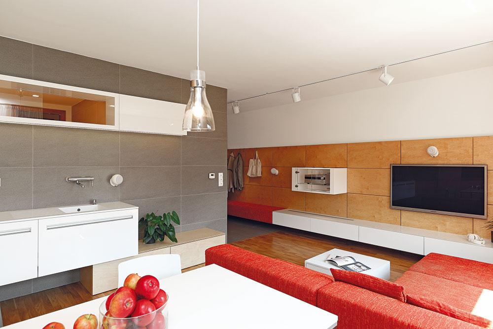 """Obývačkovú stenu vytvára nízka biela skrinka vyrobená na mieru aobklad zlakovanej javorovej preglejky – jej drevený """"dekor"""" je na rozdiel od laminátových napodobnenín skutočne dielom prírody. Za predsadenou stenou je šikovne skrytá kabeláž multimediálnej zostavy. Zpraktických dôvodov je preto preglejkový obklad odnímateľný."""