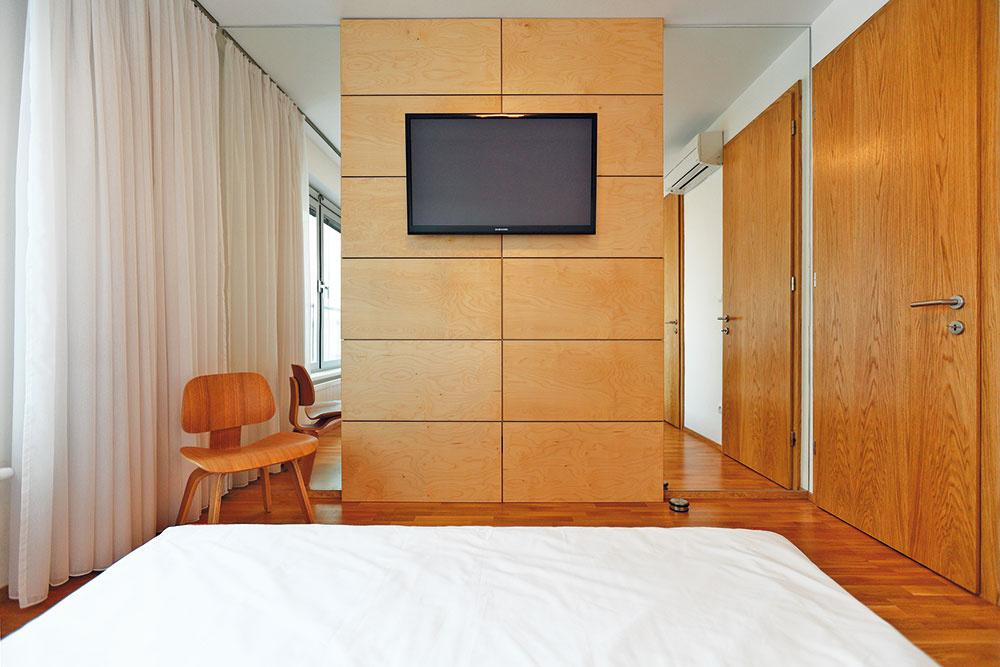 Vspálni je na stene oproti posteli použitý rovnaký obklad zlakovanej preglejky ako vo zvyšku bytu. Vďaka premyslenej kombinácii so zrkadlami sa priestor opticky predĺžil, zároveň sa však zpostele vzrkadle neuvidíte.