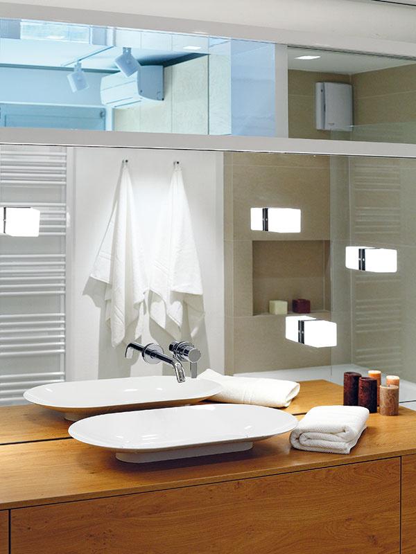 """Zrkadlová stena, vktorej sú osadené svietidlá, nástenná batéria aj skrinka pod umývadlom sú dominantným prvkom kúpeľne. Takáto efektná """"lotrovinka"""" je na montáž ajjej organizáciu omnoho náročnejšia, než by sa mohlo na prvý pohľad zdať."""