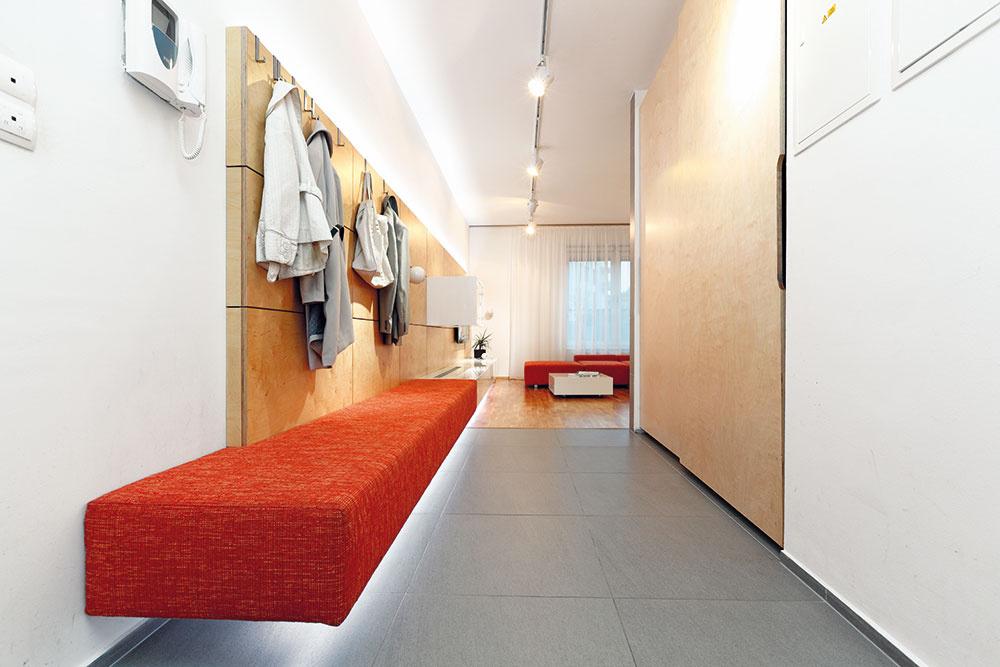 Spojenie spredsieňou opticky zväčšilo plochu denného priestoru, tento efekt ešte viac podporilo zariadenie. Drevený obklad tvorí základ obývačkovej steny, plynulo prechádza do predsiene, kde plní funkciu vešiakovej steny. Biela skrinka, ktorá vobývačke skrýva hi-fi aparatúru, sa vpredsieni mení na lavicu, na ktorej možno sedieť pri obúvaní.