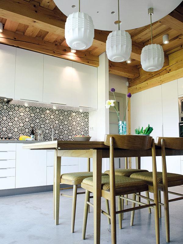 """Jeremy opisuje pocit zdomu ako harmóniu, ktorá prechádza každým miestom. """"Od bielych stien vinteriéri cez farbu dreva, leštenú betónovú podlahu až po jednoduché biele kuchyne asvietidlá zo 60. rokov."""" Práve kuchyňa snáď najjasnejšie spája moderné prvky sklasickými. Liata betónová podlaha ajednoduchá moderná kuchynská linka sú pozadím, na ktorom sa krásne vyníma síce novodobý, no ľudovým vzorom zdobený, cementový obklad zFrancúzska, dobové svietidlá aautentické stolovanie."""