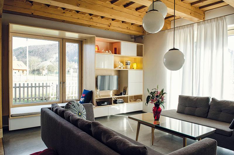 Obývacia izba rodinnej časti domu je pravdepodobne najmodernejším priestorom. Dobový šmrnc jej dodáva len pôvodný konferenčný stolík od starých rodičov. Príjemným prvkom je výklenok, ktorý vznikol rozšírením vnútorného parapetu okna. Pôsobí ako súčasť nábytku auž čoskoro sa stane neustále sa meniacim zarámovaným obrazom kvetinovej záhradky.