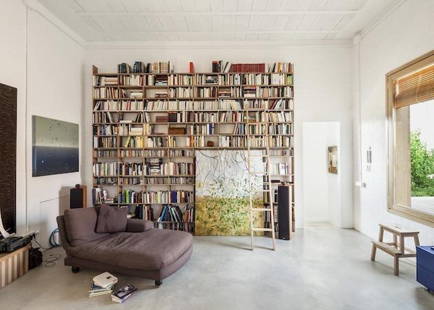 Knižnica – opäť minimalizmus: tmavý gauč vyvažuje snehovo biely interiér.
