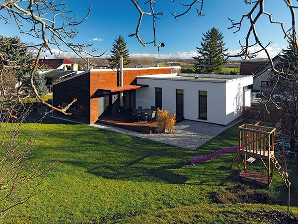 """Chránené miesto. Energeticky úsporný dom stojí na pozemku, ktorý sa končí krátkym strmým svahom. Akýsi prírodný amfiteáter tu vytvára dokonalý pocit súkromia azároveň chráni dom pred vetrom. """"Okolie Trnavy je pomerne veterné avďaka chránenému miestu má dom menšie tepelné straty,"""" upozorňuje Tomáš Guniš, architekt amajiteľ domu vjednej osobe. """"Zároveň má tento pozemok pre mňa zaujímavé industriálne dedičstvo – je to vyťažená bývalá tehelňa."""""""