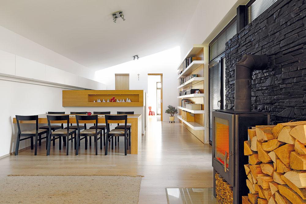 """Prevýšený denný priestor. Obývačka, jedáleň aj kuchyňa sú súčasťou jedinej dlhej miestnosti, otvorenej až po vrch pultovej strechy. """"Vďaka väčšej svetlej výške má priestor príjemnejšie proporcie. Inak by pôsobil ako tunel,"""" vysvetľuje architekt."""