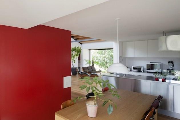 Kuchynská časť je od obývacej oddelená extravagantnou červenou stenou.