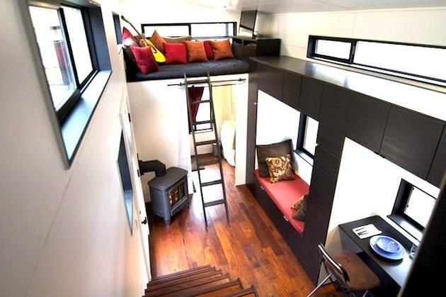Využité sú aj horné priestory, kde sa nachádza oddychový kútik. Dole je malá piecka na drevo, útulné sedenie pod oknom, kuchyňa a mini jedálenský kútik pre dvoch.