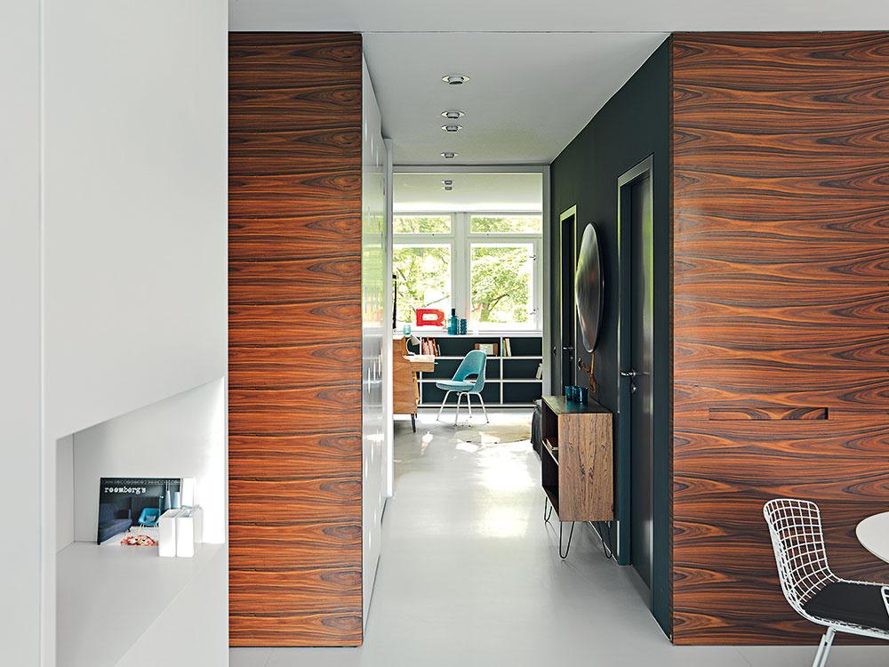 Posuvnými dverami na celú výšku miestnosti, obloženýmidyhou zpalisandra, možno oddeliť denný priestor od druhej časti bytu, vyhradenej na spálne akúpeľne. Kruhové otvory na dverách vstavanej skrine vchodbe sú odkazom na architektúru výťahovej veže.