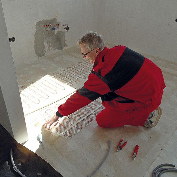 Vlokalite, kde dom stojí, nie je vybudovaný plynovod, vykurovanie preto zabezpečuje elektrický kotol. Vcelom dome sa využívajú oceľové panelové radiátory atepelnú pohodu vkuchyni akúpeľni na prízemí zabezpečujú elektrické rohože zabudované vpodlahe (na obrázku). Ako doplnkový zdroj tepla slúži teplovzdušná kozubová vložka situovaná vobývacej izbe.