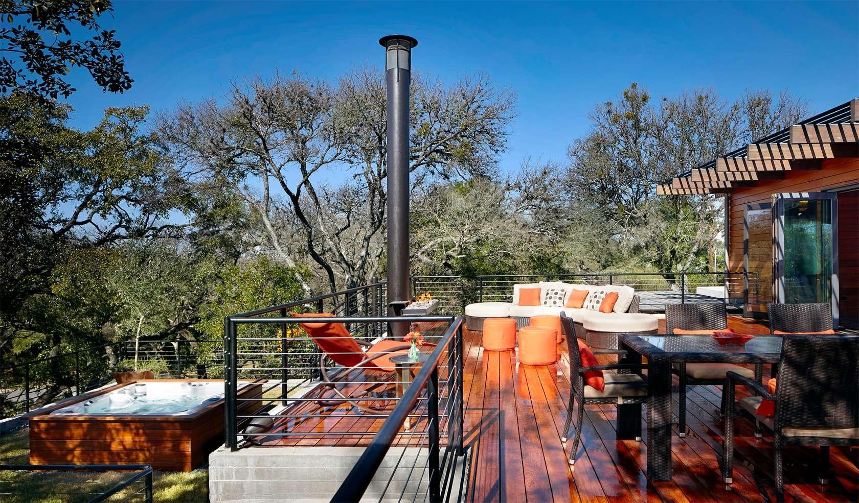 Na strešnej terase, určenej na zábavu a posedenia, sa pod stromami na zelenom trávniku nachádza aj vírivka.