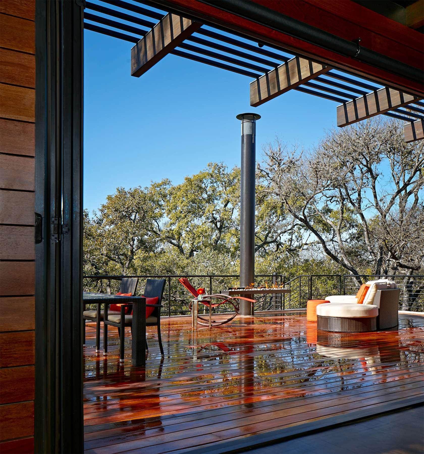 Vďaka skleneným dverám a obrovským oknám je prepojenie obývačky s exteriérom veľmi harmonické. Aj počas daždivého počasia si tak môžete vychutnať pohľad na vonkajší svet.