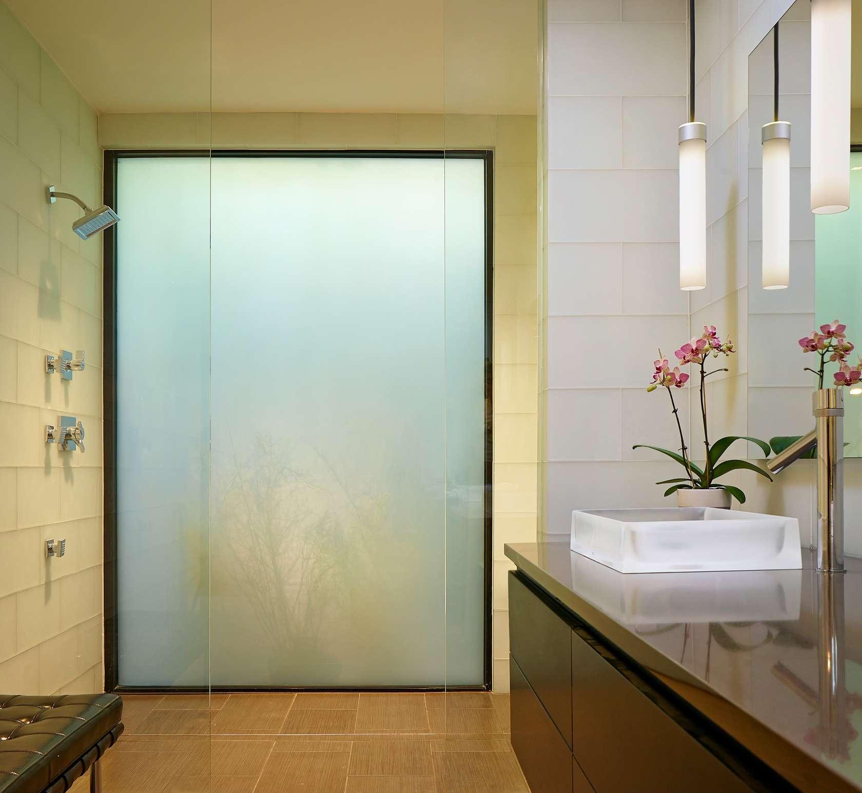 Kúpelňa v kombinácií svetlých stien a tmavého nábytku. Ružové kvety nádherne oživili tento jednoducho navrhnutý priestor. Za mliečnym sklom je veľký sprchový kút.