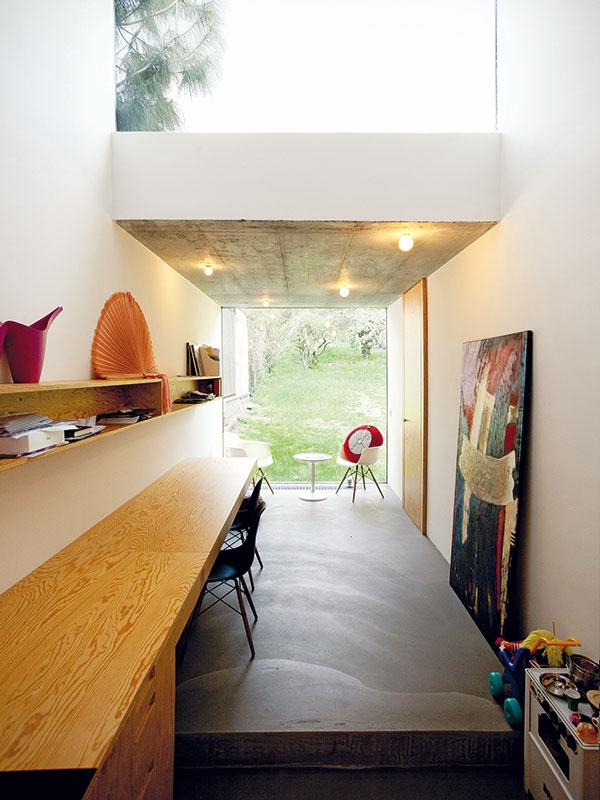 """Kuchynská linka kontinuálne prechádza do pracovného stola. Docieliť zdanlivo prirodzené však nebolo jednoduché: """"Problém bol svýškou – pracovná plocha vkuchyni má mať výšku 90 cm, pracovný stôl 75 cm. Vyriešili sme to zdvihnutím podlahy – vďaka jednému schodíku môže byť celý kuchynsko-pracovný element vjednej línii. Schodík zároveň pomáha aj pri výškovom napojení na záhradu, keďže terén smerom knej prirodzene stúpa,"""" vysvetľuje architekt."""