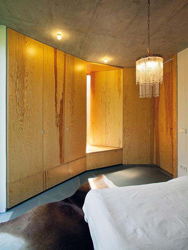 Iná skriňa Atypickosť šikmej steny vspálni architekti ešte umocnili nezvyčajným vstavaným nábytkom – skriňou, ktorou prechádza okno na terasu. Hĺbka skrine sa pritom plynulo mení – vmieste políc je menšia, vmieste vešiakov väčšia, čo vytvorilo zaujímavú geometriu drevenej steny.