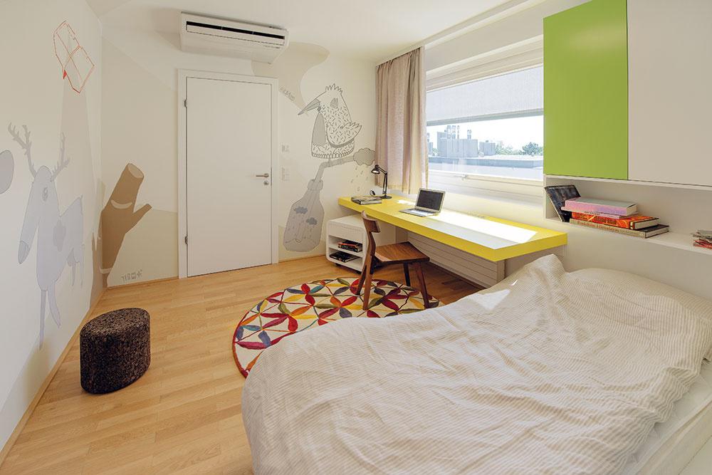 Detská izba je najodviazanejšou miestnosťou vbyte. Architekti vkusne skombinovali pestrofarebné koberce, ručne kreslenú nástennú ilustráciu vjemných tónoch smasívnou drevenou stoličkou aľanovým závesom.