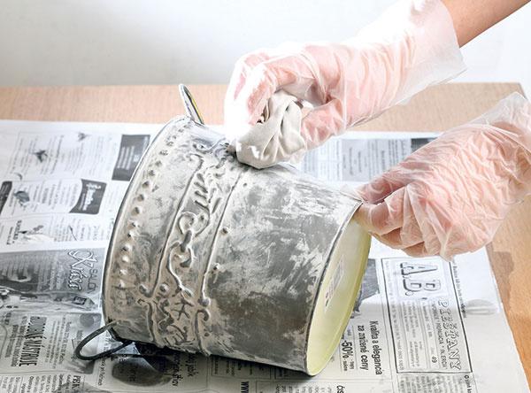 6Kým je farba ešte mokrá, jemne ju vytierajte handričkou tak, aby zospodu presvitala tmavosivá. Nechajte zaschnúť. Potom do vedierka vložte florex, naň mach apolejte vodou. Navrch poukladajte vajíčka.