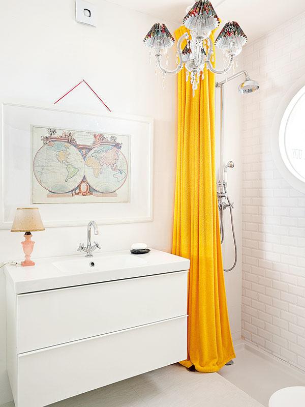 Štýlová jednotnosť. Biely základ miestnosti, výrazný žltý sprchový záves aluster, ktoré ladia sdekoračnými prvkami vsusednej obývačke, zjednotili oba priestory.